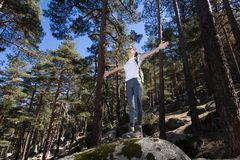 Hiker woman open arms on a great rock in forest Royalty Free Stock Photo