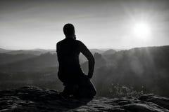 Hiker Sportsmann в черном sportswear сидит на верхней части горы и принимает остаткам туристский вахту вниз к долине утра туманно стоковое фото rf