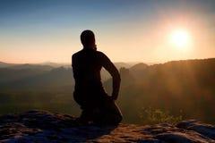 Hiker Sportsmann в черном sportswear сидит на верхней части горы и принимает остаткам туристский вахту вниз к долине утра туманно стоковые фотографии rf