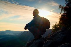 Hiker with sporty backpack sit on rocky cliff edge and watching into misty valley bellow. Sunny spring daybreak in rocky mountains Royalty Free Stock Images