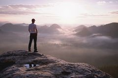 Hiker in sporty suit stand on peak in rock and watch over mist stock photos