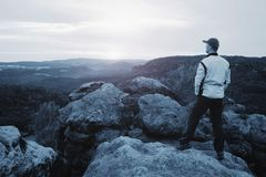 Hiker in sporty suit stand on peak in rock and watch over mist royalty free stock image