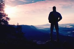 Hiker in sporty suit stand on peak in rock and watch over mist stock images
