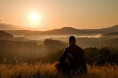 Hiker in squatting position in high grass meadow  enjoy the colorful sunrise scenery Royalty Free Stock Image