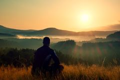 Hiker in squatting position in high grass meadow  enjoy the colorful sunrise scenery Stock Image