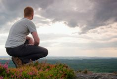 Hiker in squatting position on a rock in heather bushes, enjoy the cloudy scenery Stock Photo