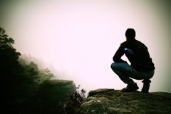 Hiker in squatting position on a rocky peak and enjoy the misty  scenery Royalty Free Stock Photos