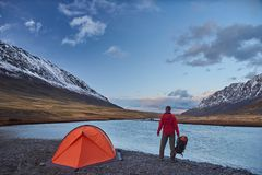 Hiker stand at camping in the mountains during springtime. Stock Photography