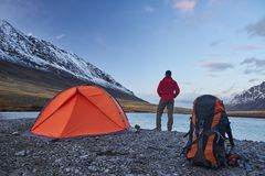 Hiker stand at camping in the mountains during springtime. Stock Image