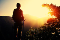 Hiker stand on mountain peak rock Stock Images