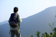 Hiker stand on mountain peak rock Stock Photography