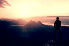 Hiker stand on the sharp corner of sandstone rock in rock empires park and watching over the misty and foggy morning valley to Sun Stock Image