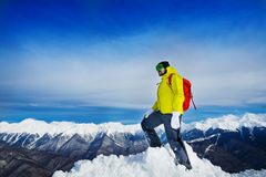 Hiker stand on top of the mountain peak. Man hiker stand on top of the mountain peak covered with snow wearing backpack Stock Photo