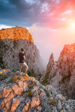 Hiker standing above the mountain canyon. Hiker standing on a cliffs edge above the mountain canyon at the sunset light with a beautiful pink fog Royalty Free Stock Photos