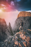 Hiker standing above the mountain canyon. Instagram stylization. Hiker standing on a cliffs edge above the mountain canyon at the sunset light with a beautiful Royalty Free Stock Photos