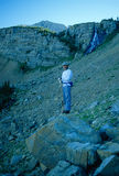 Hiker Standing Below High Mountain Cliffs and Waterfall. Wide angle vertical perspective early morning hiker standing on a big rock below high alpine mountain Stock Photo