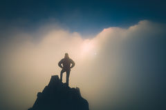 Hiker standing on a cliffs edge. Instagram stylization. Hiker standing on a cliffs edge. The top of the mountain. Colorful clouds in a light of sunrise Stock Photos