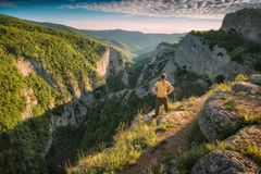 Hiker standing on a cliffs edge over a Big Crimea Canyon. At the sunset light Royalty Free Stock Photography
