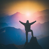 Hiker standing on a cliffs edge and rejoices sunrise. Instagram. Hiker standing on a cliffs edge with raised hands and rejoices sunrise in a mountain valley Stock Image