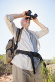 Hiker standing on country trail looking through binoculars Royalty Free Stock Photos