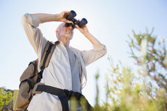 Hiker standing on country trail looking through binoculars Stock Photos