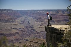Hiker standing on edge of cliff at Grand Canyon royalty free stock photos