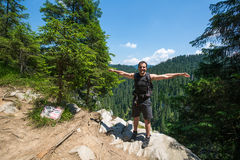 Hiker standing on the edge of a very high cliff Royalty Free Stock Photos