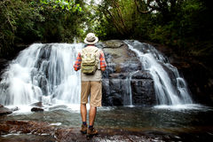 Hiker standing in front of a waterfall Stock Photos