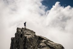 Hiker standing high up on rocky mountain peak. Hiker standing on steep rocky mountain summit without protection. Dramatic cloudy sky. Concept of reaching the Stock Image