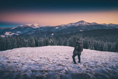 Hiker standing on a hill with snow. Instagram stylization Stock Photo