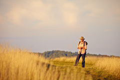 Hiker standing on meadow in late sun Stock Image