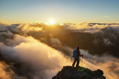A Person Standing on the Mountain with Clouds During Sunset/Sunr. A hiker is standing on the mountain with clouds during sunset/sunrise at Mount Rainier National Stock Images