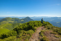 Hiker standing on mountain pass looks at the  mountain tops Royalty Free Stock Photos