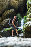 Hiker standing near a mountain river. Happy man hiker standing on a large rock near a waterfall Royalty Free Stock Image