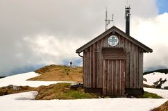 Hiker standing next to wooden hut in mountains. Royalty Free Stock Photography