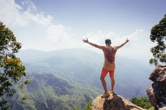 Hiker standing on a peak of mountain with raised hands.