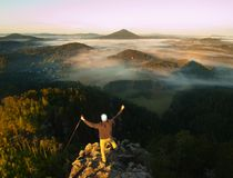Hiker is standing on the peak of sandstone rock in rock empires park and watching over the misty and foggy morning valley to Sun. Royalty Free Stock Image