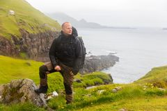 Hiker Standing in the rain On Mountain at Faroe Island With Sea In Background Royalty Free Stock Photography