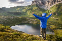 Hiker standing with raised hands near the beautiful mountain lake and enjoying view Royalty Free Stock Photo