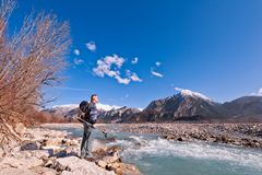 Hiker standing on river shore, looking the mountains landscape. Alps,Italy,Friuli Royalty Free Stock Image