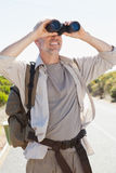 Hiker standing on road looking through binoculars Stock Photos