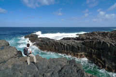 Hiker is standing on the rocky coast of El Hierro Stock Image