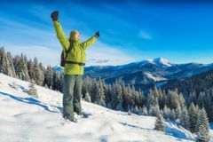 Hiker standing on a snowy hill with raised hands royalty free stock images
