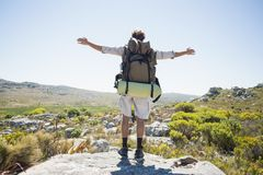 Hiker standing at the summit with arms outstretched Royalty Free Stock Photography