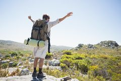 Hiker standing at the summit with arms outstretched Stock Photo