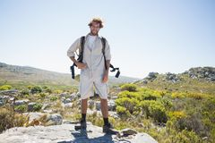 Hiker standing at the summit smiling at camera Stock Photography