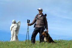 Hiker standing on the top of the Hill with his dog Royalty Free Stock Images
