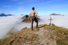 Hiker is standing on the top of a mountain royalty free stock photo