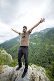 Hiker standing on top of a mountain with raised arms Stock Image