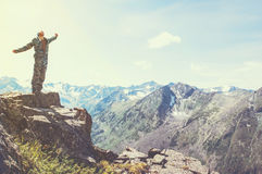 Hiker standing on top of a mountain with raised hands and enjoying sunrise Royalty Free Stock Photography